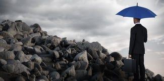 Σύνθετη εικόνα οπισθοσκόπου του επιχειρηματία που κρατά την μπλε ομπρέλα και το χαρτοφύλακα Στοκ εικόνα με δικαίωμα ελεύθερης χρήσης