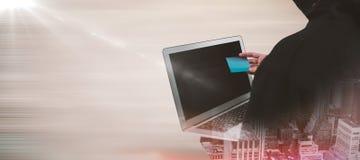 Σύνθετη εικόνα οπισθοσκόπου του χάκερ που χρησιμοποιεί το lap-top και την πιστωτική κάρτα Στοκ Εικόνα