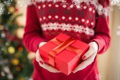 Σύνθετη εικόνα στενού επάνω μιας γυναίκας που προσφέρει ένα δώρο Στοκ Εικόνα