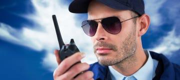 Σύνθετη εικόνα στενού επάνω του αξιωματικού ασφαλείας που μιλά στην ομιλούσα ταινία walkie Στοκ Φωτογραφία