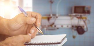 Σύνθετη εικόνα στενού επάνω του ατόμου που γράφει στο σημειωματάριο Στοκ Εικόνες
