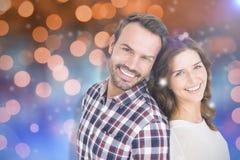 Σύνθετη εικόνα στενού επάνω του ευτυχούς νέου ζεύγους που στέκεται πλάτη με πλάτη Στοκ Εικόνες
