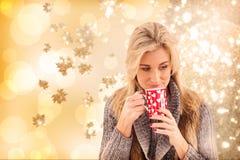 Σύνθετη εικόνα της γυναίκας στα χειμερινά ενδύματα που κρατούν μια κούπα στοκ εικόνα