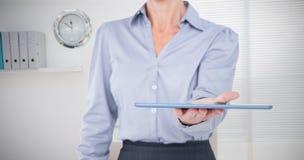 Σύνθετη εικόνα της επιχειρηματία που κρατά την ψηφιακή ταμπλέτα Στοκ φωτογραφία με δικαίωμα ελεύθερης χρήσης