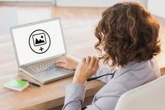 Σύνθετη εικόνα της επιχειρηματία που χρησιμοποιεί το lap-top στο γραφείο στο δημιουργικό γραφείο Στοκ Εικόνα