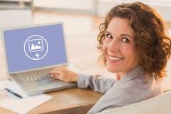 Σύνθετη εικόνα της επιχειρηματία που χρησιμοποιεί το lap-top στο γραφείο στο δημιουργικό γραφείο Στοκ Φωτογραφία