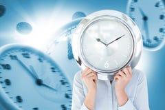 Σύνθετη εικόνα της επιχειρηματία στο κοστούμι που κρατά ένα ρολόι Στοκ Εικόνες