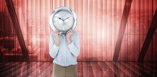 Σύνθετη εικόνα της επιχειρηματία στο κοστούμι που κρατά ένα ρολόι Στοκ Φωτογραφία