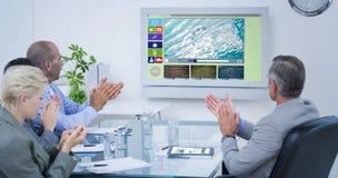 Σύνθετη εικόνα της επιχειρησιακής ομάδας που επιδοκιμάζει και που εξετάζει την άσπρη οθόνη Στοκ Εικόνες