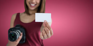 Σύνθετη εικόνα της ευτυχούς γυναίκας που παρουσιάζει δελτίο ταυτότητας κρατώντας τη κάμερα Στοκ Φωτογραφία