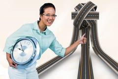 Σύνθετη εικόνα της ευχαριστημένης επιχειρηματία που κρατά ένα ρολόι Στοκ Εικόνες