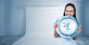 Σύνθετη εικόνα της ευχαριστημένης επιχειρηματία που κρατά ένα ρολόι Στοκ φωτογραφίες με δικαίωμα ελεύθερης χρήσης