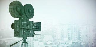 Σύνθετη εικόνα της μαύρης κάμερας εξελίκτρων ταινιών με το τρίποδο ελεύθερη απεικόνιση δικαιώματος