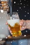 Σύνθετη εικόνα της μπύρας πλήρωσης γυαλιού εκμετάλλευσης χεριών στοκ φωτογραφία με δικαίωμα ελεύθερης χρήσης