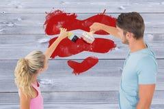 Σύνθετη εικόνα της νέας ζωγραφικής ζευγών με τις βούρτσες Στοκ φωτογραφία με δικαίωμα ελεύθερης χρήσης
