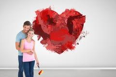 Σύνθετη εικόνα της νέας ζωγραφικής ζευγών με τον κύλινδρο Στοκ φωτογραφία με δικαίωμα ελεύθερης χρήσης