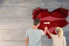 Σύνθετη εικόνα της νέας ζωγραφικής ζευγών με τον κύλινδρο Στοκ εικόνα με δικαίωμα ελεύθερης χρήσης