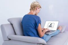 Σύνθετη εικόνα της ξανθής γυναίκας που χρησιμοποιεί το lap-top της στον καναπέ Στοκ Εικόνες