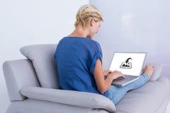 Σύνθετη εικόνα της ξανθής γυναίκας που χρησιμοποιεί το lap-top της στον καναπέ Στοκ εικόνα με δικαίωμα ελεύθερης χρήσης