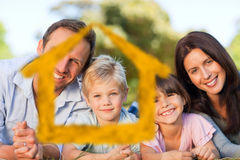 Σύνθετη εικόνα της οικογένειας που ξαπλώνει στο πάρκο Στοκ Εικόνες