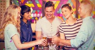 Σύνθετη εικόνα της ομάδας φίλων που ψήνουν το ποτήρι της μπύρας στο κόμμα στοκ φωτογραφίες