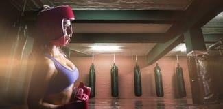 Σύνθετη εικόνα της πλάγιας όψης του θηλυκού μπόξερ με το κάλυμμα και τα γάντια Στοκ εικόνες με δικαίωμα ελεύθερης χρήσης