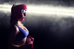 Σύνθετη εικόνα της πλάγιας όψης του θηλυκού μπόξερ με το κάλυμμα και τα γάντια Στοκ Εικόνες