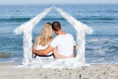 Σύνθετη εικόνα της στοργικής συνεδρίασης ζευγών στην άμμο στην παραλία Στοκ εικόνα με δικαίωμα ελεύθερης χρήσης