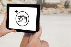 Σύνθετη εικόνα της συνεδρίασης γυναικών στην παραλία που χρησιμοποιεί το PC ταμπλετών Στοκ Εικόνες