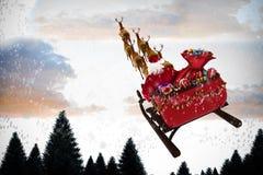 Σύνθετη εικόνα της υψηλής άποψης γωνίας Άγιου Βασίλη που οδηγά στο έλκηθρο κατά τη διάρκεια των Χριστουγέννων στοκ εικόνα