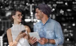 Σύνθετη εικόνα της χαμογελώντας γυναίκας και του άνδρα που κρατούν ένα τηλέφωνο και μια ταμπλέτα Στοκ Εικόνες