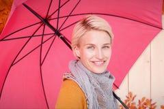 Σύνθετη εικόνα της χαμογελώντας γυναίκας που κρατά μια ομπρέλα Στοκ Εικόνα