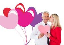 Σύνθετη εικόνα της όμορφης καρδιάς εγγράφου εκμετάλλευσης ατόμων που παίρνει ένα φιλί από τη σύζυγο Στοκ Φωτογραφίες
