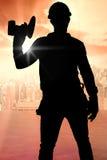 Σύνθετη εικόνα της handyman φορώντας ζώνης εργαλείων κρατώντας το τρυπάνι δύναμης στοκ εικόνα