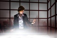 Σύνθετη εικόνα της redhead επιχειρηματία που χρησιμοποιεί το διαλογικό γραφείο Στοκ Φωτογραφία