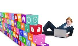 Σύνθετη εικόνα της redhead επιχειρηματία που χρησιμοποιεί το lap-top της Στοκ Εικόνα