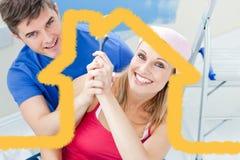 Σύνθετη εικόνα του αγκαλιάσματος του ζεύγους που έχει τη διασκέδαση χρωματίζοντας ένα δωμάτιο Στοκ εικόνες με δικαίωμα ελεύθερης χρήσης