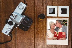 Σύνθετη εικόνα του ανώτερου ατόμου που δίνει ένα φιλί και ένα χριστουγεννιάτικο δώρο στη σύζυγό του Στοκ Φωτογραφία