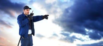 Σύνθετη εικόνα του αξιωματικού ασφαλείας που δείχνει μακριά μιλώντας στην ομιλούσα ταινία walkie Στοκ Εικόνα