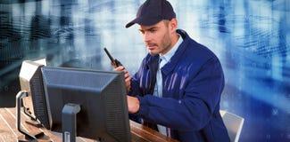 Σύνθετη εικόνα του αξιωματικού ασφαλείας που φαίνεται παρατηρώντας τα όργανα ελέγχου υπολογιστών και μιλώντας στο walki Στοκ Φωτογραφία