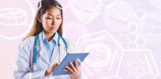 Σύνθετη εικόνα του ασιατικού γιατρού που χρησιμοποιεί την ταμπλέτα Στοκ εικόνα με δικαίωμα ελεύθερης χρήσης