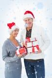 Σύνθετη εικόνα του εορταστικού ώριμου ζεύγους στα χειμερινά ενδύματα που κρατά τα δώρα Στοκ φωτογραφίες με δικαίωμα ελεύθερης χρήσης