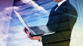 Σύνθετη εικόνα του επιχειρηματία με το ρολόι που χρησιμοποιεί το PC ταμπλετών Στοκ Φωτογραφία