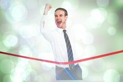 Σύνθετη εικόνα του επιχειρηματία που διασχίζει τη γραμμή τερματισμού σφίγγοντας την πυγμή Στοκ Εικόνα