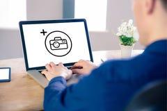 Σύνθετη εικόνα του επιχειρηματία που χρησιμοποιεί το lap-top στην αρχή Στοκ Εικόνα