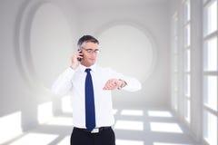 Σύνθετη εικόνα του επιχειρηματία στο τηλέφωνο που εξετάζει το wristwatch του Στοκ Εικόνα