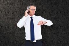 Σύνθετη εικόνα του επιχειρηματία στο τηλέφωνο που εξετάζει το wristwatch του Στοκ εικόνα με δικαίωμα ελεύθερης χρήσης