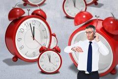 Σύνθετη εικόνα του επιχειρηματία στο τηλέφωνο που εξετάζει το wristwatch του Στοκ Εικόνες
