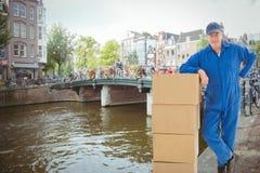 Σύνθετη εικόνα του ευτυχούς ατόμου παράδοσης που κλίνει στο σωρό των κουτιών από χαρτόνι Στοκ Εικόνες