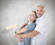 Σύνθετη εικόνα του ευτυχούς ζεύγους που αγκαλιάζει και που κρατά τον κύλινδρο χρωμάτων Στοκ εικόνα με δικαίωμα ελεύθερης χρήσης
